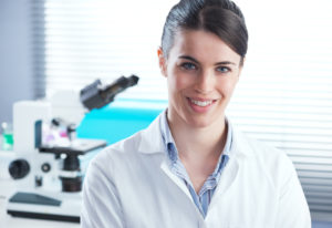 Confident female researcher in the chemistry lab with microscope and laboratory glassware on background.